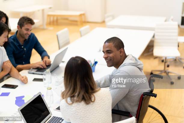 disabled man sitting in a wheelchair at business meeting - disabled access stock photos and pictures