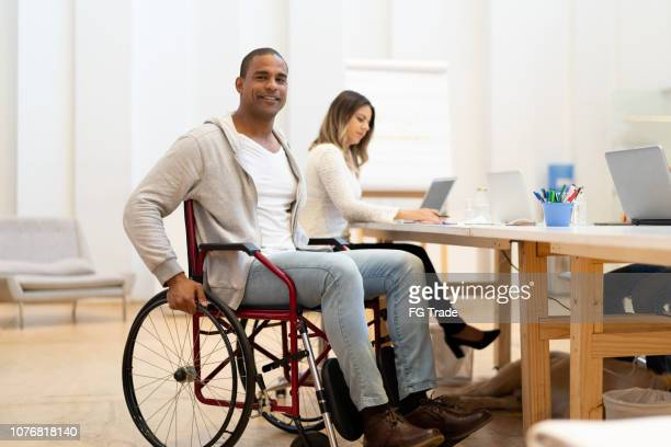 disabled man sitting in a wheelchair at workplace - wheelchair stock pictures, royalty-free photos & images