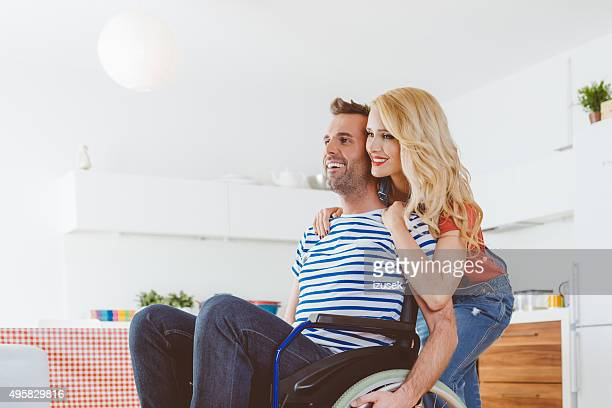 Disabled man sitting in a wheelchair, his wife embracing him