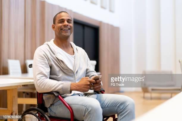 com deficiência homem sentado em uma cadeira de rodas usando móveis no local de trabalho - cadeira de rodas elétrica - fotografias e filmes do acervo