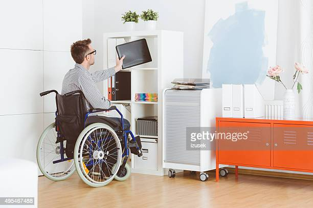 Behinderten Mann sitzt in einem wheelchat wie zu Hause fühlen.