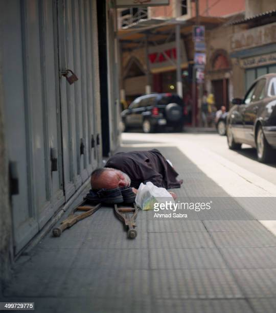 Disabled man sleeping on the streets of Tripoli Lebanon, using his shoes as pillows.