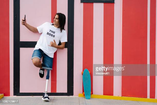 disabled man taking selfie while standing against red wall - leaning disability stock pictures, royalty-free photos & images