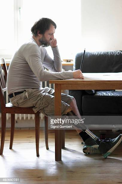 Disabled man using laptop in living room