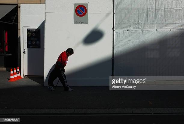 Disabled man walks by using his walking stick. The diagonal shadows emphasize his struggle.
