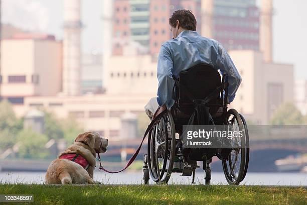 disabled man with his service dog in a park - quadriplegic fotografías e imágenes de stock