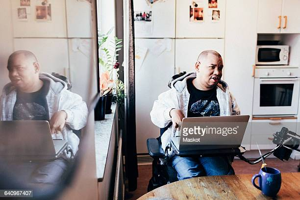 Disabled man with laptop in recording studio