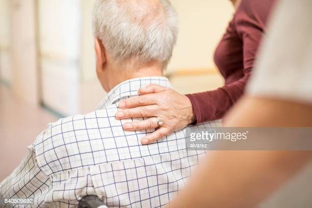 disabled man with wife in hospital - hand on shoulder stock pictures, royalty-free photos & images