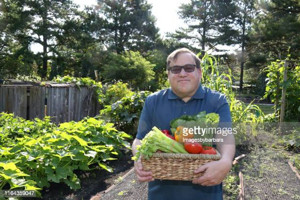 disabled man works in the garden - learning disability stock pictures, royalty-free photos & images