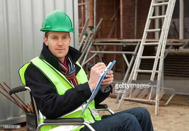 Homme écrivant sur presse-papiers aux personnes à mobilité réduite