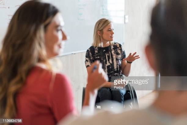disabled manager explaining strategy in office - differing abilities female business stock pictures, royalty-free photos & images