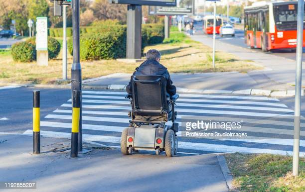 disabled mature man in wheelchair on pedestrian crossing - animated zebra stock pictures, royalty-free photos & images
