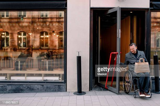 disabled mature man with shopping bag leaving store in city - shop window stock pictures, royalty-free photos & images