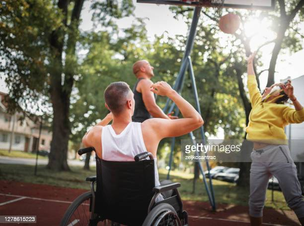 disabled men playing basketball with friends - friendly match stock pictures, royalty-free photos & images