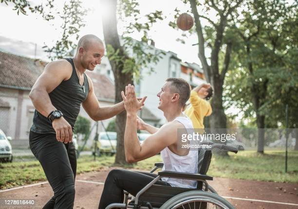 disabled men playing basketball with friends - basketball sport stock pictures, royalty-free photos & images