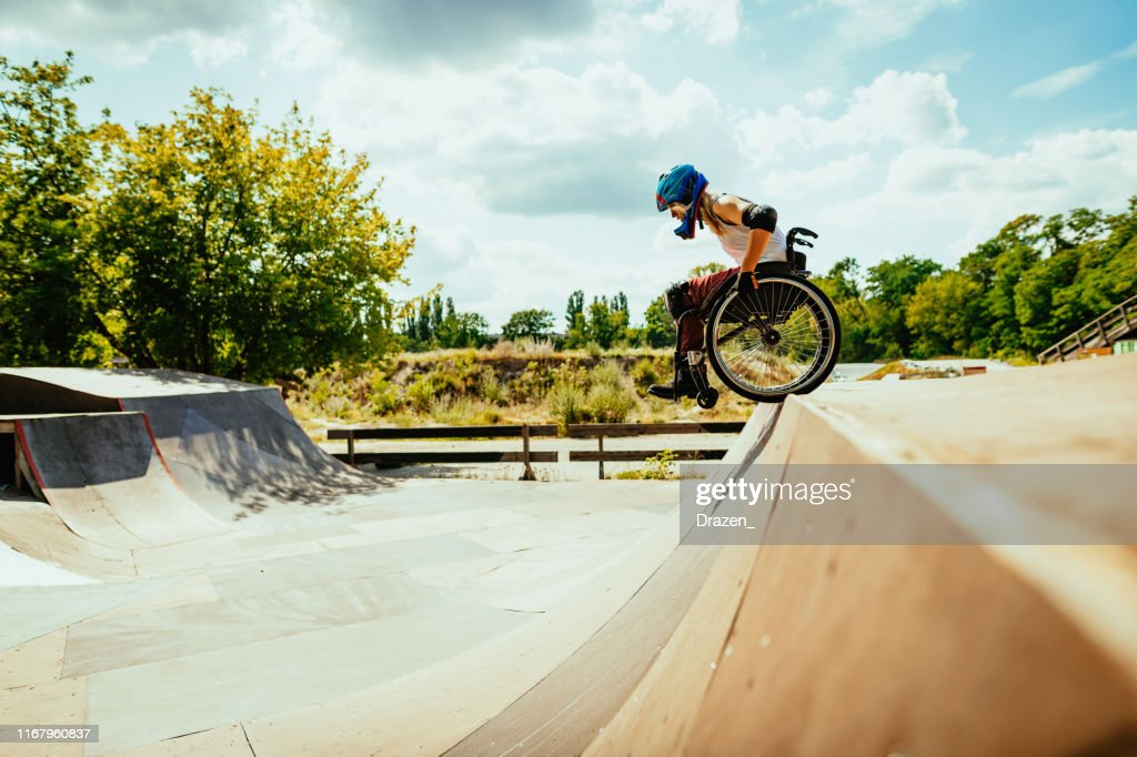 Disabled millennial woman in wheelchair rolls down the hills in skate park : Stock Photo