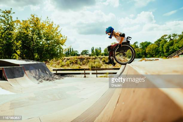 disabled millennial woman in wheelchair rolls down the hills in skate park - coraggio foto e immagini stock