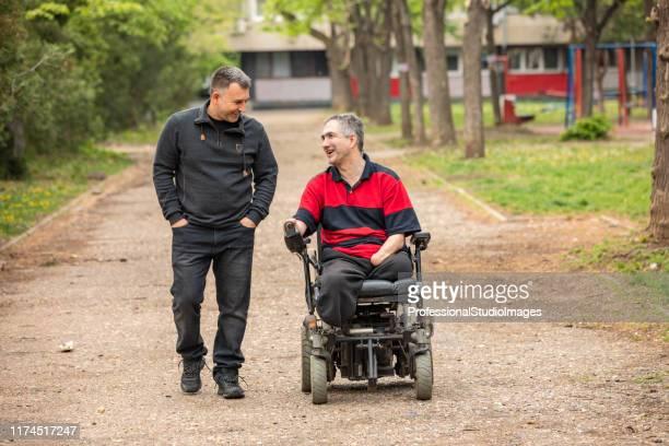 gehandicapte persoon in elektrische rolstoel in een openbaar park met een vriend - human interest stockfoto's en -beelden