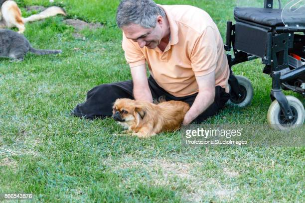 Personne handicapée est assis sur l'herbe et de jouer avec le petit chien.