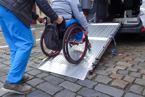 Disabled person on wheelchair using car lift 1186773260