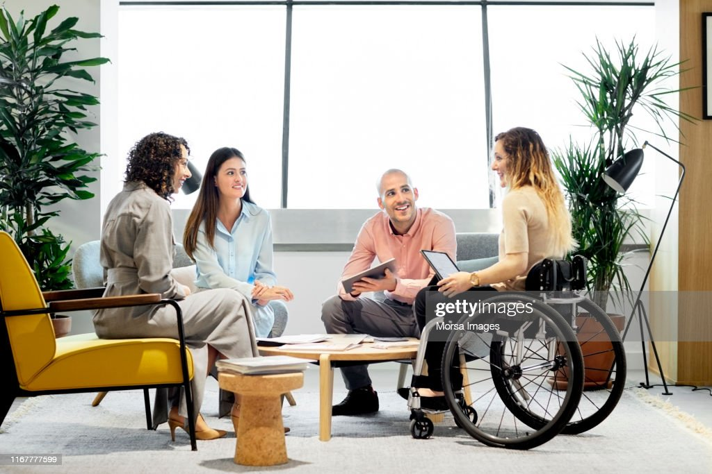 Disabled professional with coworkers in meeting : Stock Photo