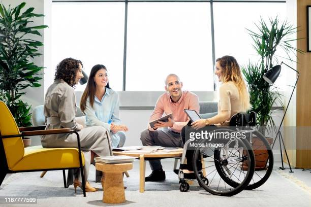 disabled professional with coworkers in meeting - minder validen stockfoto's en -beelden