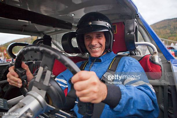 Disabled race car driver with spinal cord injury in a modified car with removable steering wheel, gas and brake hand controls and push button automatic transmission