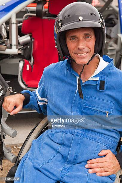 Disabled race car driver with spinal cord injury in wheelchair with his modified race car