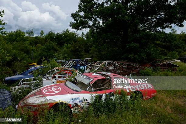 Disabled race cars are seen in a stockcar graveyard behind the catch fence prior to the NASCAR Cup Series Pocono 350 at Pocono Raceway on June 28,...