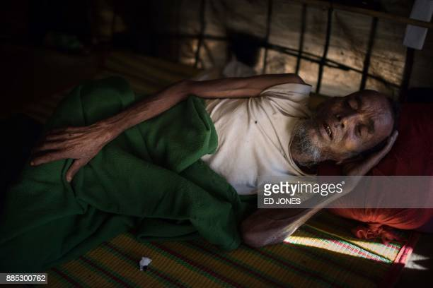 A disabled Rohingya man lies in a shelter in the the Kutupalong refugee camp in Cox's Bazar on December 4 2017 Rohingya are still fleeing into...
