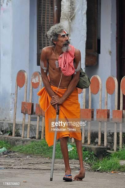 A disabled sadhu walks towards temple to offer prayers on August 28 2013 in Ayodhya India Three days after Vishwa Hindu Parishad field Parikarma...