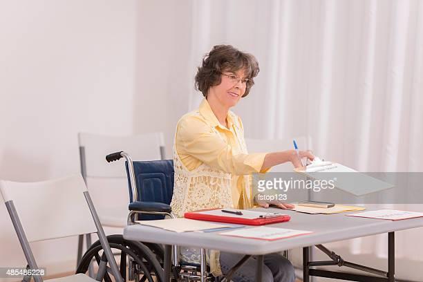 Com deficiência senior Adulto mulher na conferência ou Registo de Eleitor tabela.