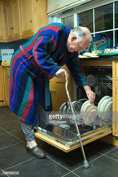 Disabled senior man empties dishwasher