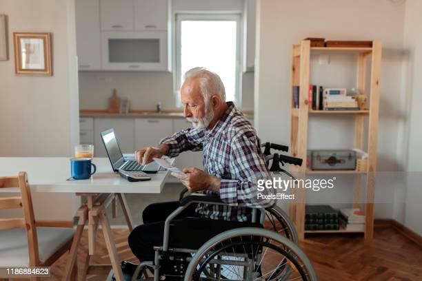 homme aîné handicapé dans un fauteuil roulant travaillant de la maison - personnes avec déficiences photos et images de collection