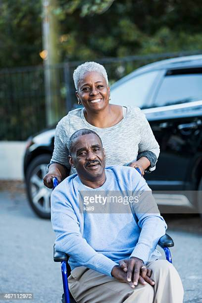 Disabled senior man in wheelchair with his devoted wife