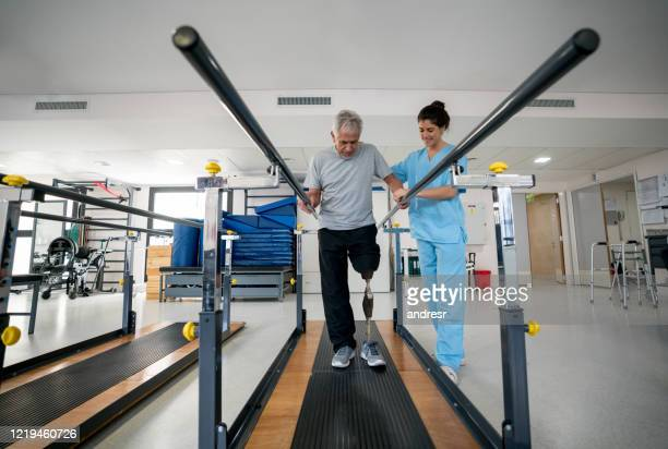 disabled senior man wearing a prosthetic and doing physical therapy - amputee stock pictures, royalty-free photos & images