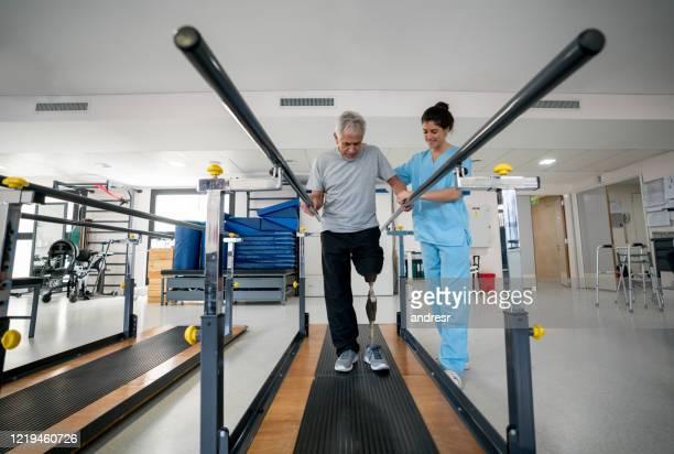 behinderter senior, der eine prothese trägt und physiotherapie macht - amputee woman stock-fotos und bilder