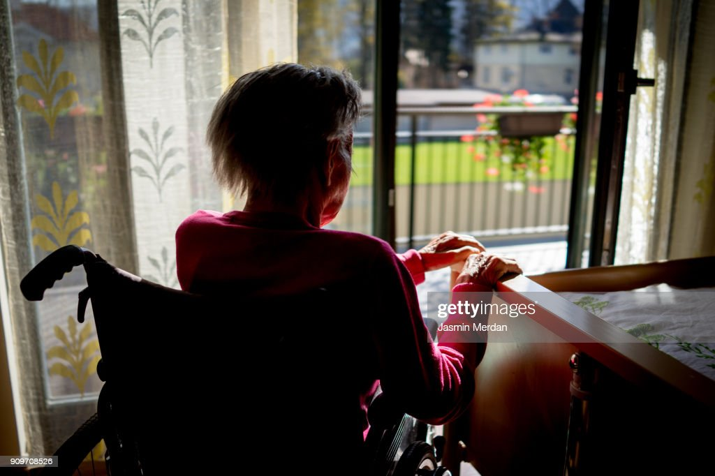 Disabled senior woman in wheelchair at home in living room : Stock Photo