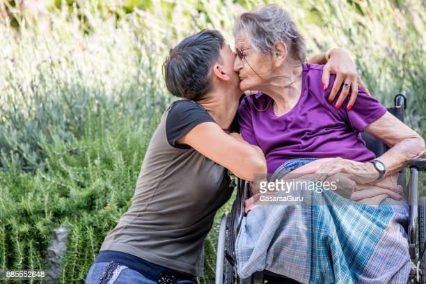 disabled senior woman on wheelchair is always happy to receive visits - leg kissing stock photos and pictures