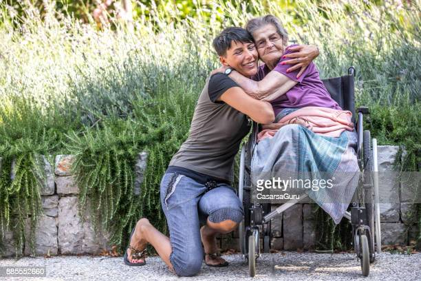 disabled senior woman on wheelchair is always happy to receive visits - amputee woman stock photos and pictures