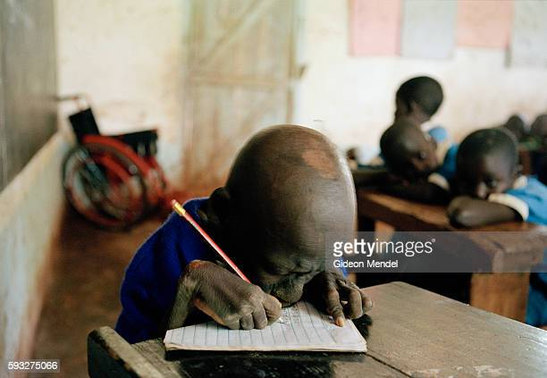 Disabled seventeenyearold Saitoti Onyango writing in his exercise book during a class at Oriang School Saitoti who cannot speak and can barely see...