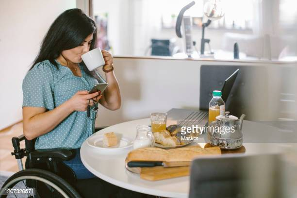 disabled woman drinking coffee while using smart phone at dining table in room - persons with disabilities stock pictures, royalty-free photos & images