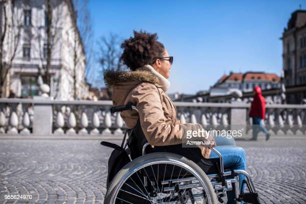 Disabled woman in a wheelchair enjoying the sun in the city