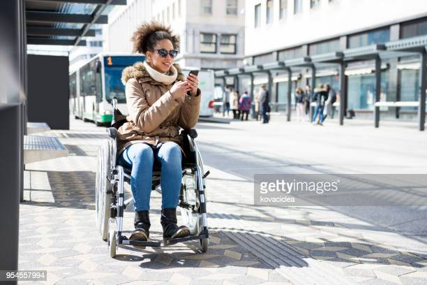 disabled woman in a wheelchair waiting at a bus station and using smart phone - assistive technology stock pictures, royalty-free photos & images