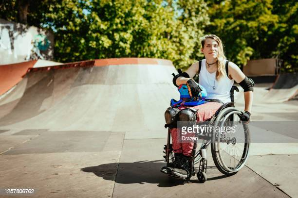 disabled woman in wheelchair doing stunts in skate park - teenage girls stock pictures, royalty-free photos & images