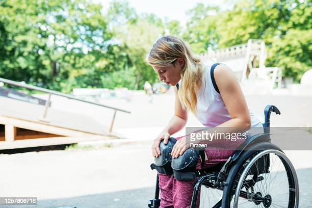 disabled woman in wheelchair prepares for stunts in skate park - stunt stock pictures, royalty-free photos & images