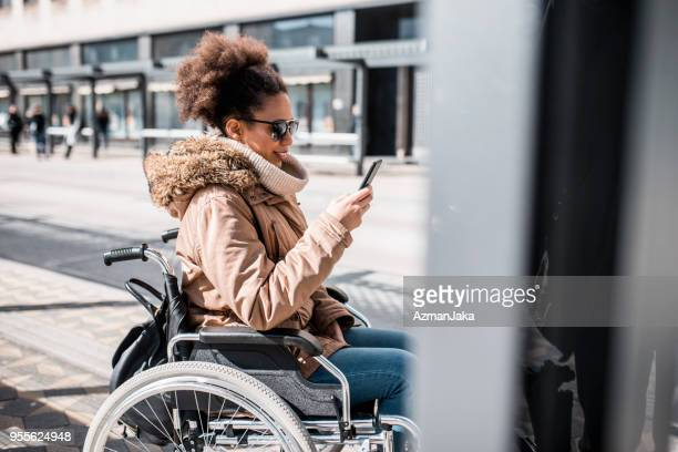 Disabled woman in wheelchair using smart phone and waiting for a bus