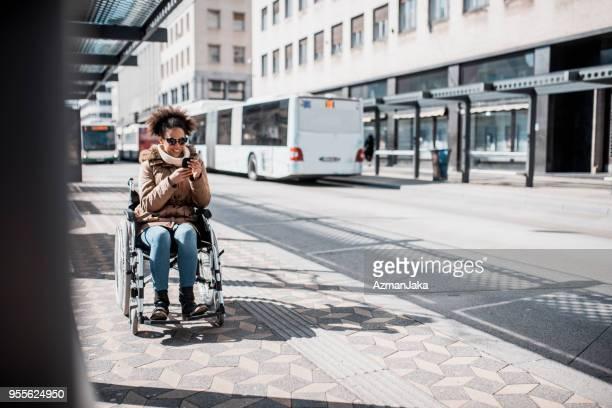 mulher com deficiência em cadeira de rodas usando telefone inteligente e esperando um ônibus - cadeira de rodas elétrica - fotografias e filmes do acervo