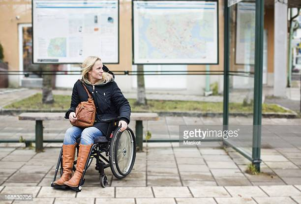 disabled woman in wheelchair waiting at bus stop - activiteit stockfoto's en -beelden