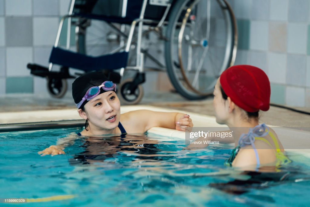 Disabled woman training for competitive swimming is listening to advice from her coach : ストックフォト